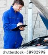 Handsome mechanic writing on a clipboard standing in front of a car - stock photo