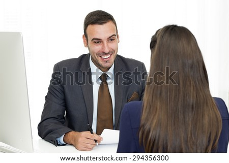 Handsome mid adult manager with beard  dressed in a suit sitting at the desk opposite young woman and talking.  - stock photo