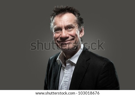 Handsome Middle Age Business Man in Suit with Cheesy Silly Grin on Grey Background High Contrast Grunge Look