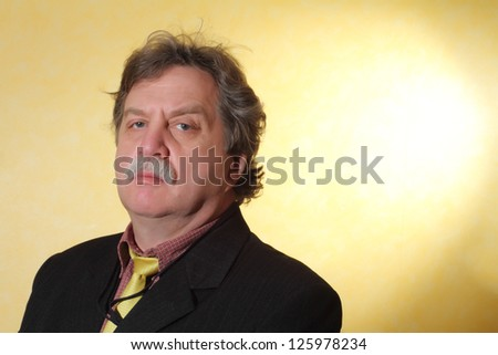Handsome middle age business man wearing a suit on a yellow  background