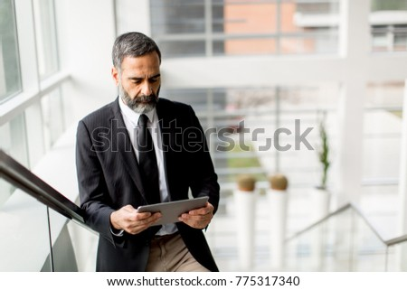 Handsome middle age businessman with digital tablet in the modren office