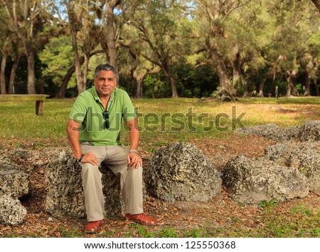 Handsome middle age hispanic man in a park setting. - stock photo