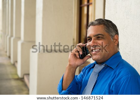 Handsome middle age Hispanic man in an urban setting with a wireless phone. - stock photo