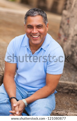 Handsome middle age Hispanic man in casual clothing outdoors.