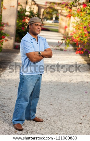 Handsome middle age Hispanic man in casual clothing wearing a stylish hat outdoors. - stock photo