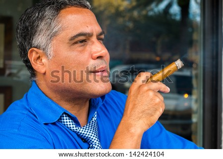 Handsome middle age Hispanic man smoking a cigar. - stock photo