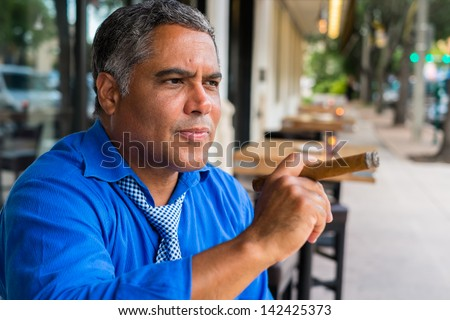 Handsome middle age Hispanic man smoking a cigar outdoors in a restaurant.