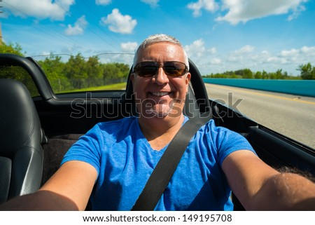 Handsome middle age man driving a convertible automobile on the highway.