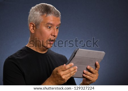 Handsome middle age man holding a tablet computer in a studio portrait.