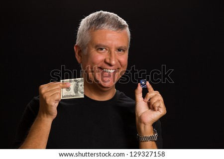 Handsome middle age man in a studio portrait holding a Las Vegas craps game dice and hundred dollar bill.