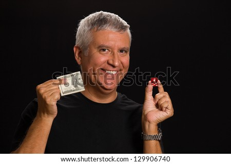 Handsome middle age man in a studio portrait holding a Las Vegas craps game dice and hundred dollar bill. - stock photo