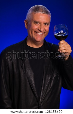 Handsome middle age man in a studio portrait wearing a leather sports coat and a glass of red wine.