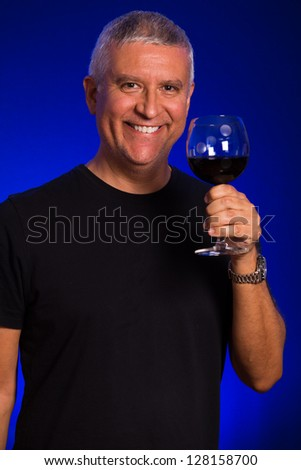 Handsome middle age man in a studio portrait with a glass of red wine. - stock photo