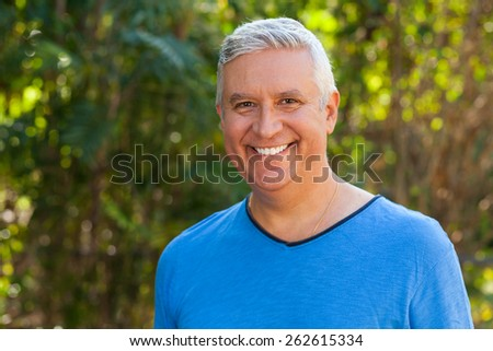 Handsome middle age man outdoor portrait with a green background.