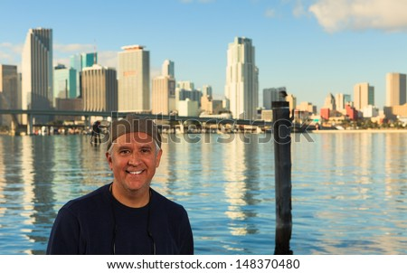 Handsome middle age man outdoor portrait with city skyline in the background.