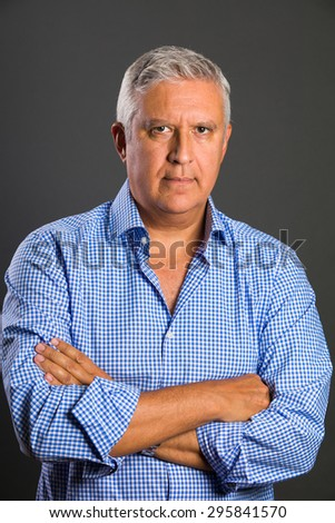 Handsome middle age man studio portrait on a gray background.