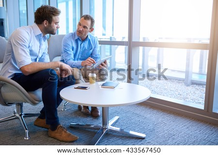Handsome middle-aged business executive sitting with a younger coworker in a bright modern office, explaining some information to him on a digital tablet - stock photo