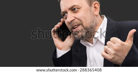Handsome middle-aged business man speaks on a mobile phone and gesturing on dark background with copy-space - stock photo