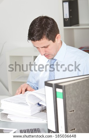 Handsome middle-aged businessman hard at work doing research at his desk reading through information in large office binders - stock photo