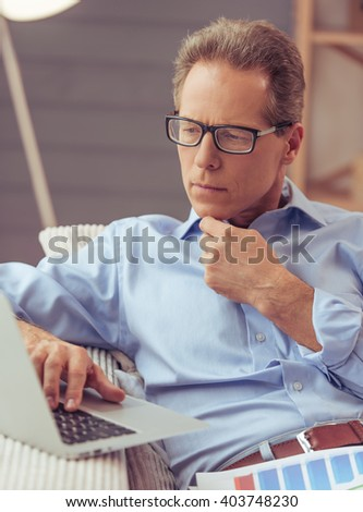 Handsome middle aged businessman in classic shirt and eyeglasse is using a laptop while working at home