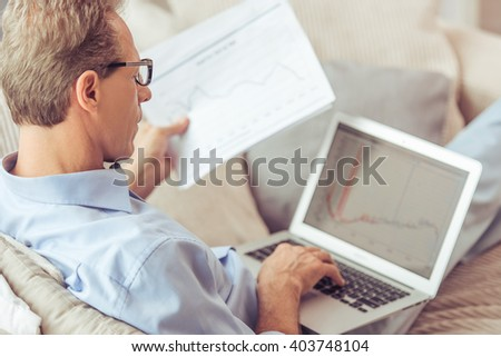 Handsome middle aged businessman in eyeglasses is using a laptop and holding documents while working at home