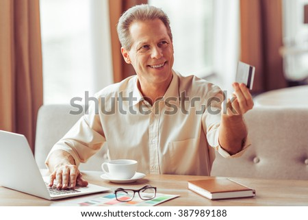 Handsome middle aged businessman is paying with a credit card for business lunch at the restaurant - stock photo
