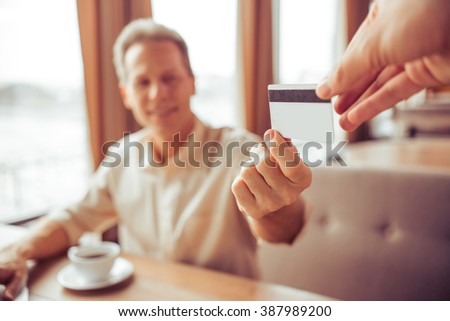 Handsome middle aged businessman is paying with a credit card for business lunch at the restaurant, close-up - stock photo