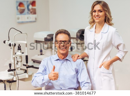 Handsome middle aged man at the ophthalmologist on consultation. Young beautiful female doctor standing near. Both smiling