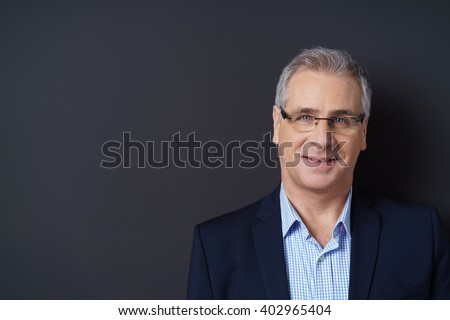 Handsome middle-aged man in eyeglasses posing against a dark background with copy space looking at the camera with a thoughtful smile - stock photo
