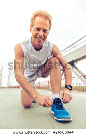 Handsome middle aged man in sports uniform is lacing his shoes, looking at camera and smiling during morning run - stock photo