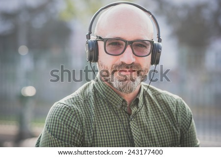 handsome middle aged man listening music in the city - stock photo