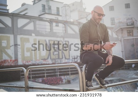 handsome middle aged man listening to music in the city - stock photo
