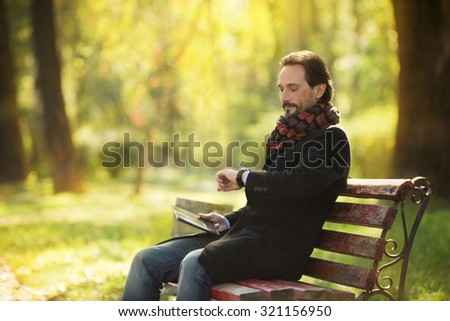 Handsome middle-aged man resting on the bench outdoors. Man holding tablet PC and looking at his watch, because he is waiting for someone. - stock photo