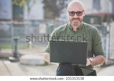 handsome middle aged man using notebook in the city - stock photo