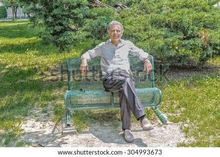 Handsome middle-aged man with salt pepper hair dressed with white shirt, blue slacks and beige moccasins is resting on a bench in city park keeping his arms opened: he smiles showing a reassuring look