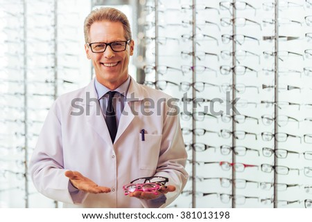 Handsome middle aged ophthalmologist offering eyeglasses, looking at camera and smiling while standing in his office - stock photo
