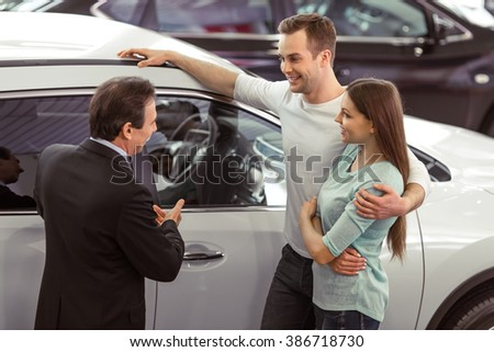 Handsome middle aged salesman is showing a car to beautiful young couple in a motor show - stock photo