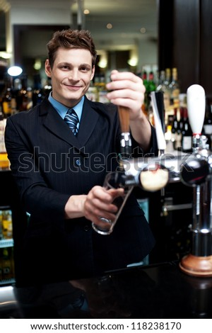 Handsome mixologist putting ice into tall glass. Bar decorated with bottles in the background - stock photo