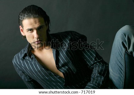 Handsome Model posing in shadows. Black background