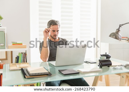 handsome modern architect wearing a tee-shirt, thinking about a project on his laptop, sitting at his desk, his office is contemporary et luminous - stock photo