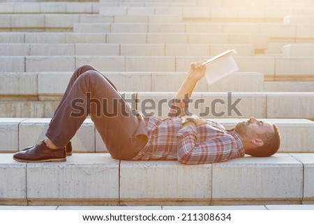 Handsome modern businessman reading outdoors lying on stairs - stock photo