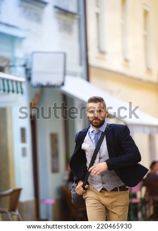Handsome modern hipster businessman with bag hurrying to work - stock photo