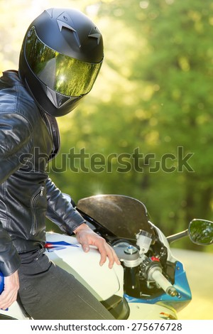 Handsome motorcyclist posing on his super sport motorcycle. Lens flare. Soft focus.