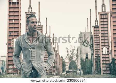 Handsome muscular blond man standing in city setting or former industrial environment - stock photo