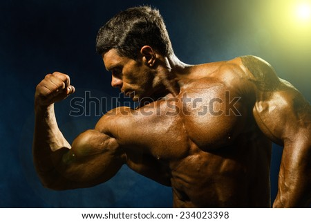 Handsome muscular bodybuilder demonstrates his muscles. Beauty of the male body illuminated by yellow light right - stock photo