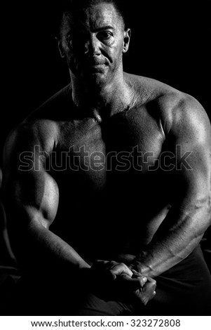 Handsome muscular bodybuilder. Muscular young man lifting weights on dark background.