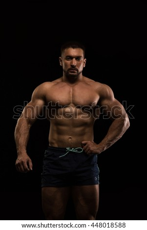 handsome muscular bodybuilder posing on a black background