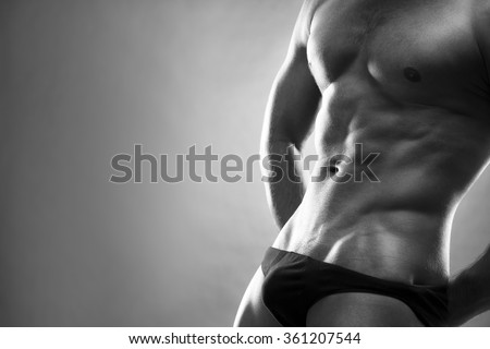 Handsome muscular bodybuilder posing on gray background. Low key black and white studio shot with copy space. Sexy male body - stock photo