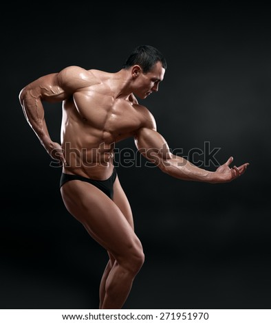 Handsome muscular bodybuilder posing over black background. Isolated with clipping path. - stock photo