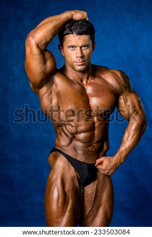 Handsome muscular bodybuilder posing over blue background. - stock photo